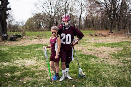 Brother and sister wearing lacrosse uniforms Stock Photo - Premium Royalty-Free, Code: 614-07652488