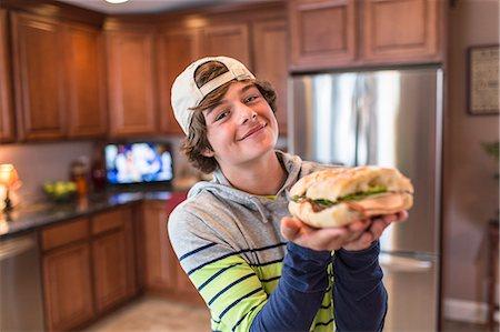 Teenage boy in kitchen holding sandwich Stock Photo - Premium Royalty-Free, Code: 614-07652480