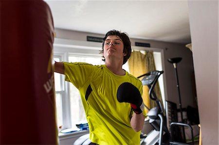 Teenage boy wearing boxing gloves Stock Photo - Premium Royalty-Free, Code: 614-07652482
