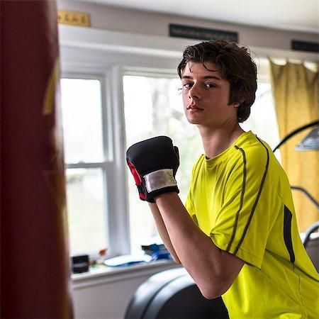 Teenage boy wearing boxing gloves Stock Photo - Premium Royalty-Free, Code: 614-07652483