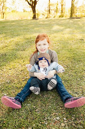 Portrait of girl and baby brother on grass in park Stock Photo - Premium Royalty-Free, Code: 614-07652494