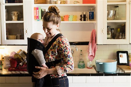day - Mid adult mother with baby son in sling in kitchen Stock Photo - Premium Royalty-Free, Code: 614-07652505