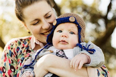 Close up of mid adult mother carrying baby son in park Stock Photo - Premium Royalty-Free, Code: 614-07652502