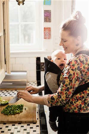 Mid adult mother preparing food with baby son in sling Stock Photo - Premium Royalty-Free, Code: 614-07652503
