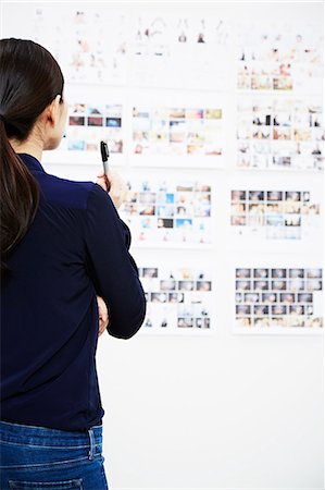 designer (female) - Young woman looking at photographs in studio Stock Photo - Premium Royalty-Free, Code: 614-07652521