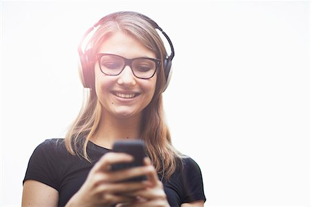 Young woman wearing headphones using smartphone Stock Photo - Premium Royalty-Free, Code: 614-07652557