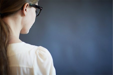 Young woman wearing glasses, studio shot Stock Photo - Premium Royalty-Free, Code: 614-07652551