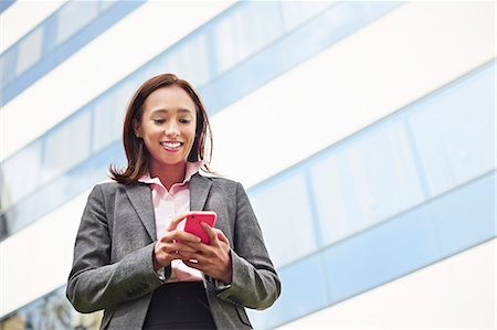 Young female businesswoman texting on smartphone outside office Stock Photo - Premium Royalty-Free, Code: 614-07652567