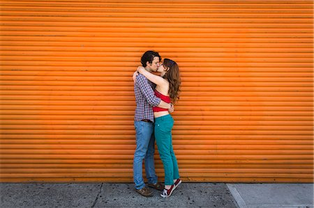 Romantic couple kissing in front of orange shutter Stock Photo - Premium Royalty-Free, Code: 614-07708165