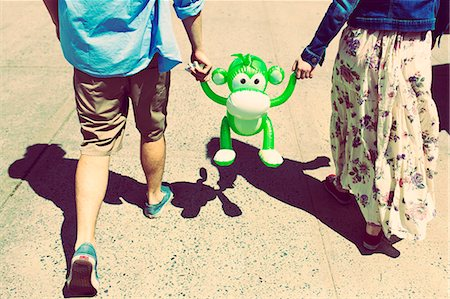 Cropped rear view of couple holding hands with inflatable monkey Stock Photo - Premium Royalty-Free, Code: 614-07708168