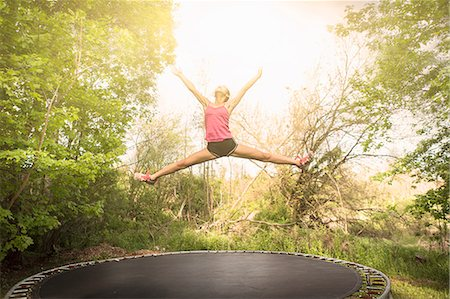 Teenage girl doing star jump on trampoline, outdoors Stock Photo - Premium Royalty-Free, Code: 614-07708258