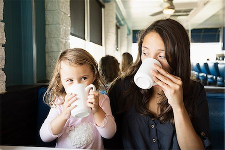 Mother and toddler drinking mugs of coffee in diner Stock Photo - Premium Royalty-Free, Code: 614-07708348
