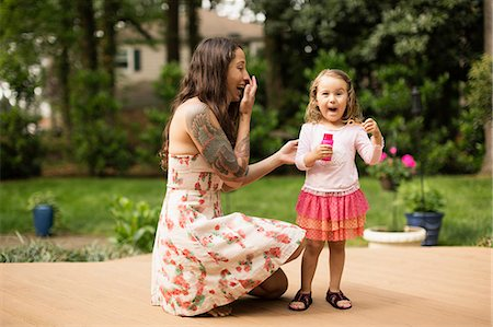 Mother and toddler daughter blowing bubbles in garden Stock Photo - Premium Royalty-Free, Code: 614-07708340