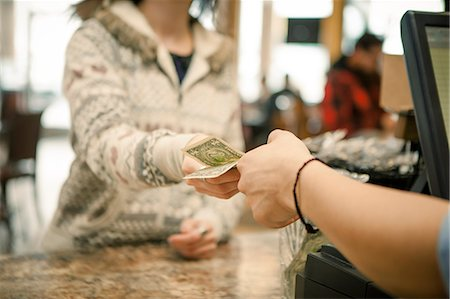 Female customer handing payment to waiter over cafe counter Stock Photo - Premium Royalty-Free, Code: 614-07735159