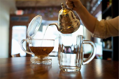 pouring - Female hand pouring tea on cafe counter Stock Photo - Premium Royalty-Free, Code: 614-07735164