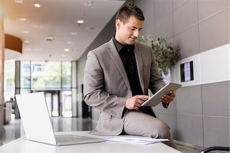 Mid adult businessman on office desk using digital tablet Foto de stock - Sin royalties Premium, Código: 614-07735172