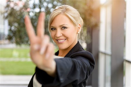 Portrait of young businesswoman making victory sign Stock Photo - Premium Royalty-Free, Code: 614-07735182