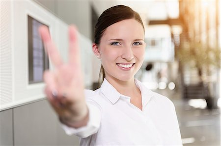 Portrait of young businesswoman holding up hand in victory sign Stock Photo - Premium Royalty-Free, Code: 614-07735196