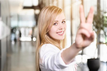 Portrait of confident young businesswoman making victory sign with hand Stock Photo - Premium Royalty-Free, Code: 614-07735190
