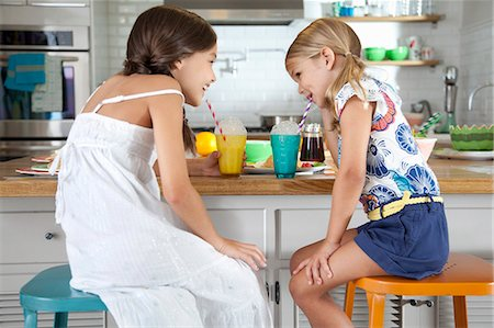 Two mischievous sisters blowing bubbles through straws at breakfast bar Stock Photo - Premium Royalty-Free, Code: 614-07735222