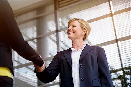 Mature businesswoman shaking hands with client Stock Photo - Premium Royalty-Free, Code: 614-07735233