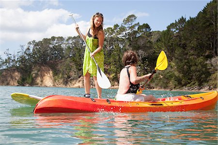 Senior woman and daughter playfighting from kayak and paddleboard Stock Photo - Premium Royalty-Free, Code: 614-07735240