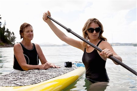 Senior woman and daughter wading with paddleboard at sea Stock Photo - Premium Royalty-Free, Code: 614-07735242