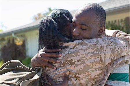 Close up of female soldier hugging husband on homecoming Stock Photo - Premium Royalty-Free, Code: 614-07735261