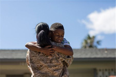 Rear view of female soldier hugging son on homecoming Stock Photo - Premium Royalty-Free, Code: 614-07735263