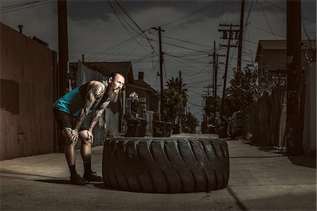 Mid adult man standing by large tire Stock Photo - Premium Royalty-Free, Code: 614-07735295