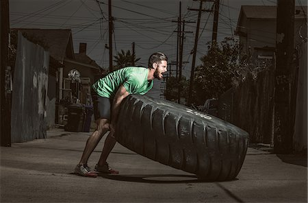 Young adult man lifting large tire, crossfit exercise Stock Photo - Premium Royalty-Free, Code: 614-07735296