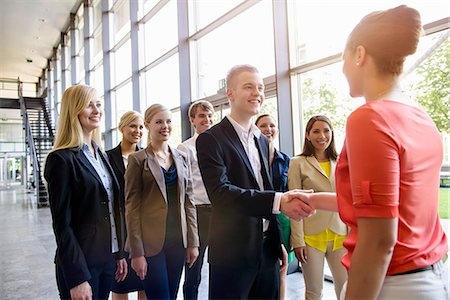 Team of business men and women greeting client in office Stock Photo - Premium Royalty-Free, Code: 614-07735350