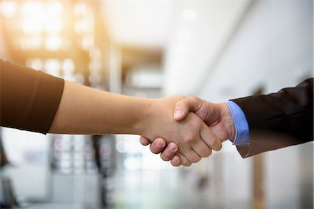 Close up of businesswomen and businessman shaking hands in office Stock Photo - Premium Royalty-Free, Code: 614-07735364