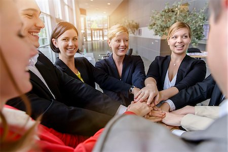 Over shoulder view of business team placing hands on top of each other in office Stock Photo - Premium Royalty-Free, Code: 614-07735360