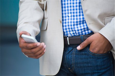 device - Cropped torso shot of young businessman on city street using smartphone Stock Photo - Premium Royalty-Free, Code: 614-07735449