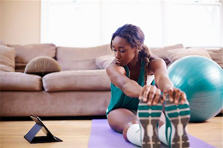 exercising - Young woman exercising on sitting room floor whilst looking at digital tablet Stock Photo - Premium Royalty-Free, Code: 614-07735458