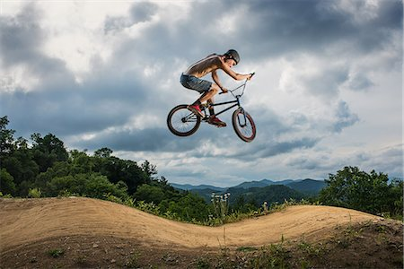 Young man doing BMX trick on rural pump track Stock Photo - Premium Royalty-Free, Code: 614-07735496