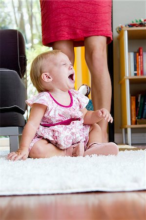 Legs of mid adult mother next to screaming baby daughter Stock Photo - Premium Royalty-Free, Code: 614-07735508