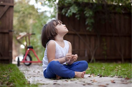 Four year old girl sitting on garden path gazing upward Stock Photo - Premium Royalty-Free, Code: 614-07735500