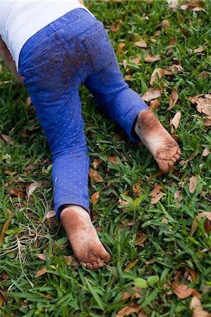 Four year old girl waist down crawling on garden grass Stock Photo - Premium Royalty-Free, Code: 614-07735502