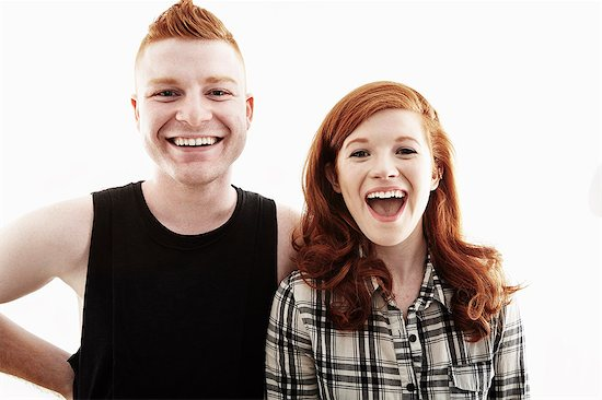 Studio portrait of red haired young couple laughing Stock Photo - Premium Royalty-Free, Image code: 614-07735548