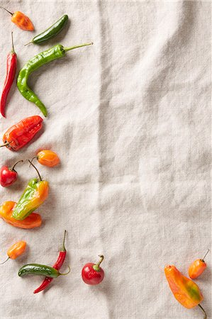 Selection of summer chilli peppers on an ivory linen surface Stockbilder - Premium RF Lizenzfrei, Bildnummer: 614-07735617