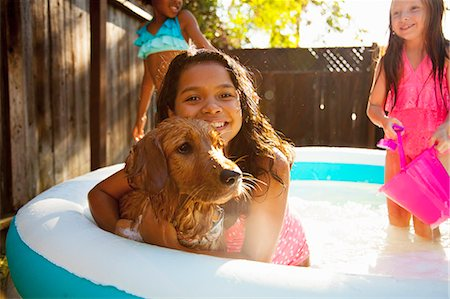 preteen swimsuit - Three girls and a dog in garden paddling pool Stock Photo - Premium Royalty-Free, Code: 614-07768069