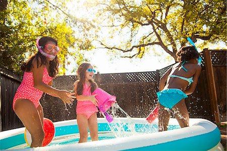 Three girls playing and splashing in garden paddling pool Stock Photo - Premium Royalty-Free, Code: 614-07768074