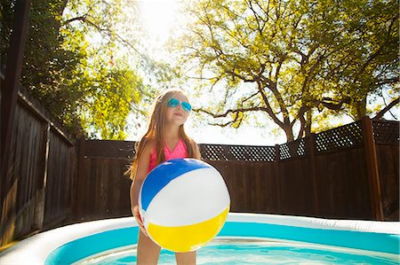 elementary age - Girl holding beachball in garden paddling pool Stock Photo - Premium Royalty-Free, Code: 614-07768075