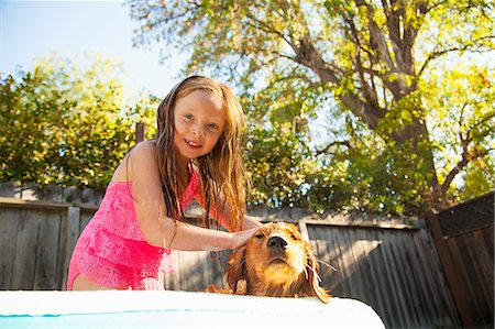 elementary age - Portrait of girl petting dog in garden paddling pool Stock Photo - Premium Royalty-Free, Code: 614-07768070