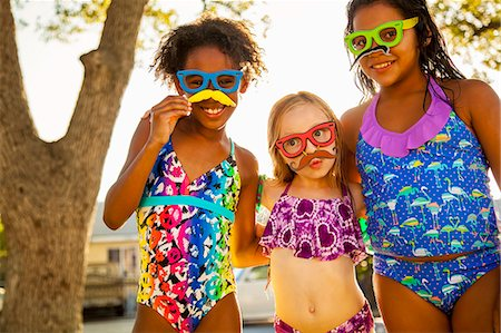 preteen bathing suit - Portrait of girls in spectacles and mustaches in garden Stock Photo - Premium Royalty-Free, Code: 614-07768087