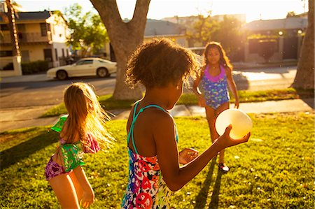 Three girls playing with water balloons in garden Stock Photo - Premium Royalty-Free, Code: 614-07768088