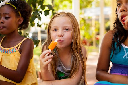 preteen swimsuit - Portrait of three girls eating ice lollies in garden Stock Photo - Premium Royalty-Free, Code: 614-07768081