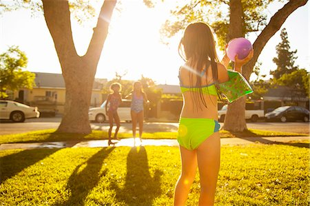 Girl chasing friends with water balloon in garden Stock Photo - Premium Royalty-Free, Code: 614-07768083